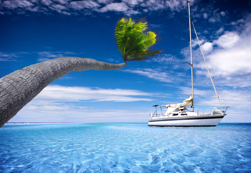 Sailing Boat in tropical lagoon with bending palm tree in the foreground